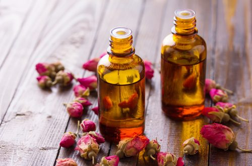 Essential aroma oil with roses on wooden background. Selective focus.